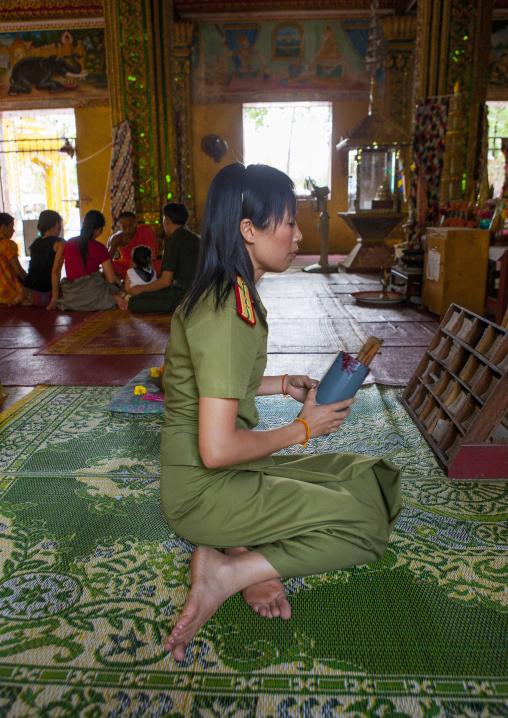 Army woamn praying in vat si muang, Vientiane, Laos
