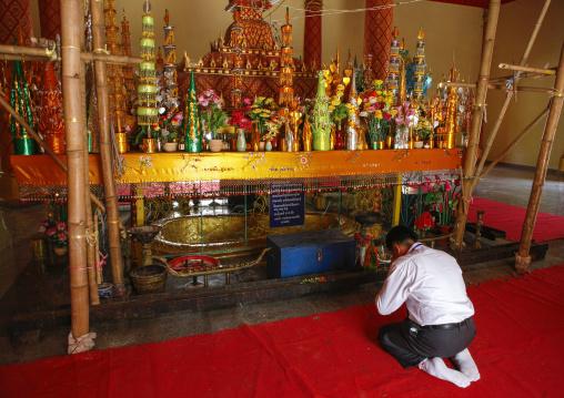 Man praying in a temple, Vientiane, Laos