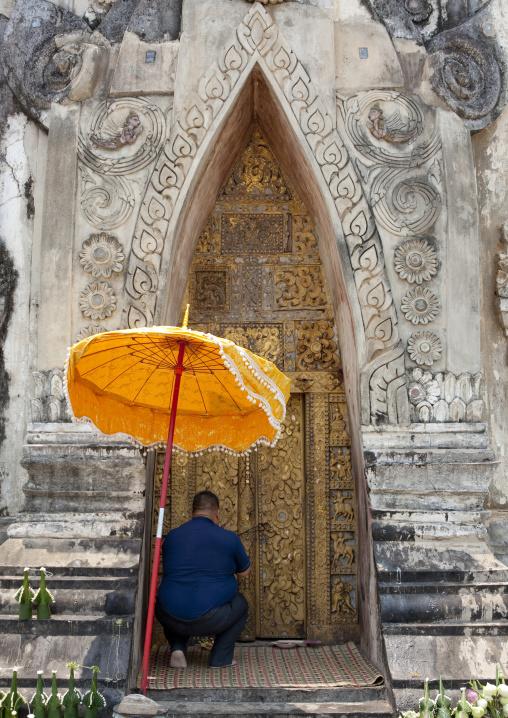 Man praying in front of a stupa in hang, Savannakhet, Laos