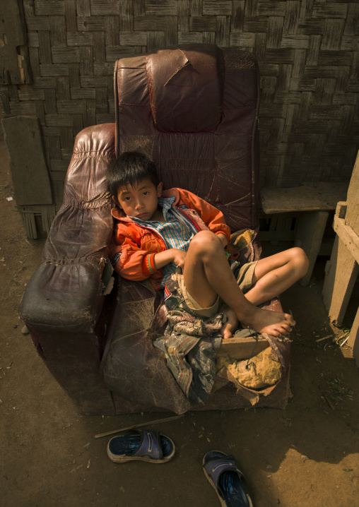 Boy sitting in an old chair, Louang namtha, Laos