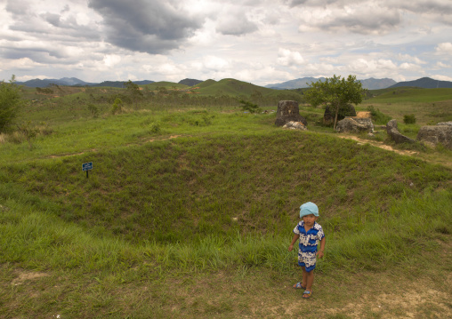 Child in from of a bomb crater at plain of jars, Phonsavan, Laos