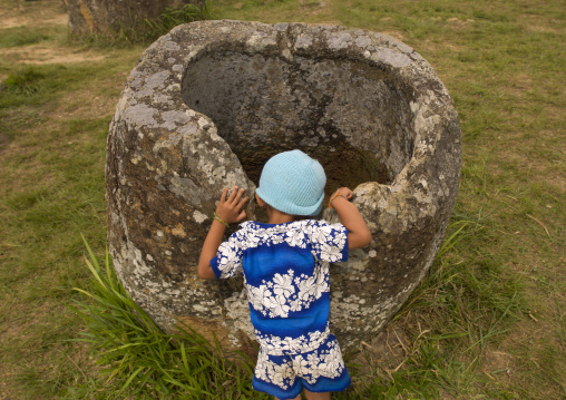 Little girl looking inside a jar, Plain of jars, Phonsavan, Laos