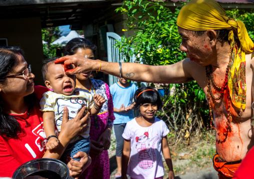 Hindu Devotee In Annual Thaipusam Religious Festival In Batu Caves Blessing A Baby, Southeast Asia, Kuala Lumpur, Malaysia