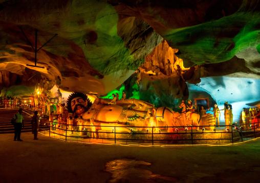 Tourists Looking At Laying Hindu Statue In The Batu Caves, Southeast Asia, Kuala Lumpur, Malaysia