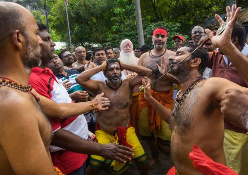 A Devotee Cheek Is Pierced With A Skewer By A Priest At Thaipusam Hindu Festival At Batu Caves, Southeast Asia, Kuala Lumpur, Malaysia