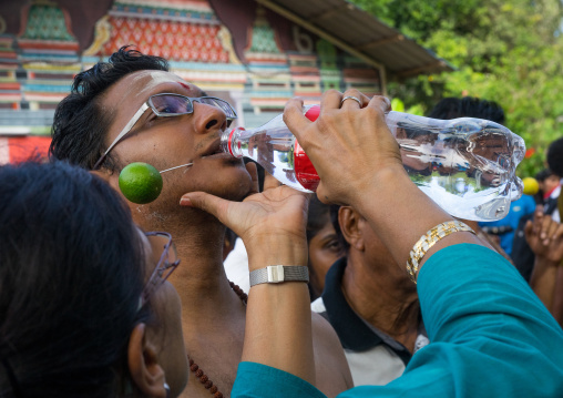 Woman Giving Water To An Hindu Devotee In Annual Thaipusam Religious Festival In Batu Caves, Southeast Asia, Kuala Lumpur, Malaysia