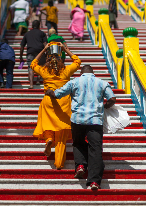 Hindu Devotee Woman Climbing Stairs With Water Jug On Her Head In Annual Thaipusam Religious Festival In Batu Caves, Southeast Asia, Kuala Lumpur, Malaysia