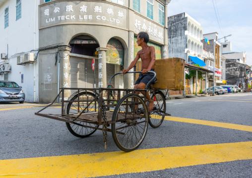 Skinny Man Rickshaw Pedalling Through Chinatown, Penang Island, George Town, Malaysia