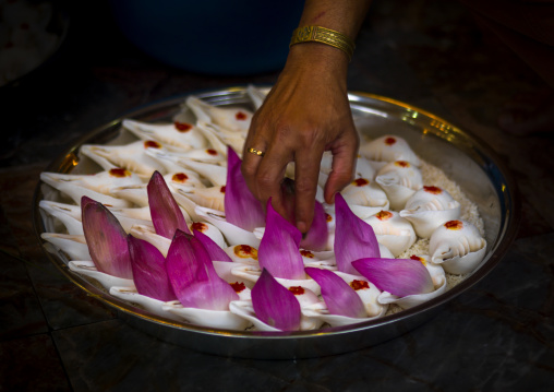 Woman Putting Flowers Petals On Shells For A Religious Offering, Malacca, Malaysia