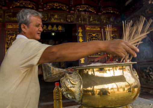 Man Putting Incense Sticks In Cheng Hoon Teng Temple, Malacca, Malaysia