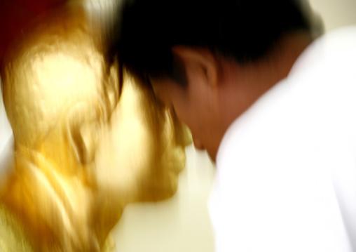 Man Praying In Front Of A Golden Statue In Shwedagon Pagoda, Rangoon, Myanmar