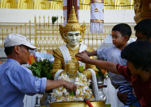 People putting water on a statue in shwedagon pagoda, Rangoon, Myanmar