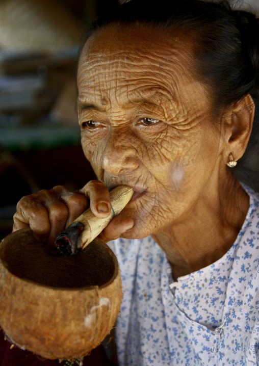 Elderly woman smoking cigar, Bagan, Myanmar