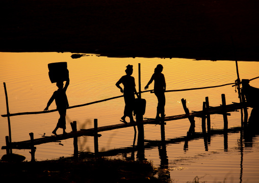 Women crossing a brige at sunset in bagan, Myanmar