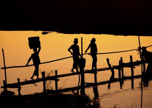 Women Crossing A Brige At Sunset In Bagan, Myanmar