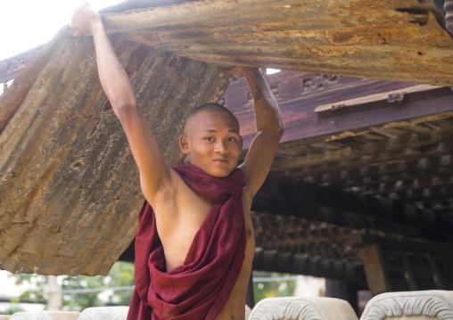 Novice Monk In Nat Taung Kyaung Monastery Carrying Furniture, Bagan, Myanmar