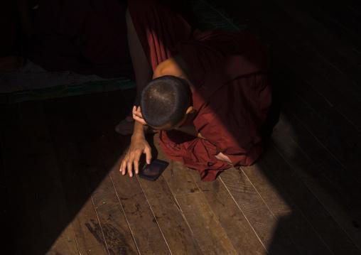 Novice Buddhist In Shwe Yan Pyay Monastery Playing With His Mobile Phone, Myanmar