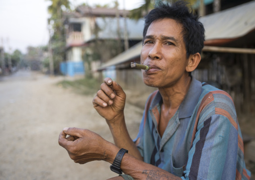 Man smoking a cigar, Thandwe, Myanmar