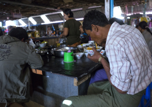 Man eating in a restaurant inside a market, Thandwe, Myanmar