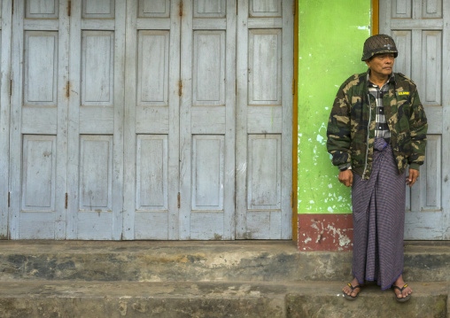 Man in army uniform standing in the street, Sittwe, Myanmar