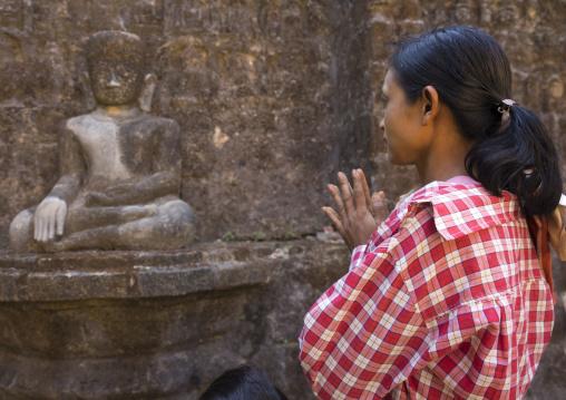 Woman praying inside kothaung temple, Mrauk u, Myanmar