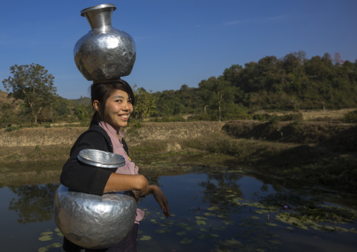 Woman walking with water backet on her head mrauk u, Myanmar