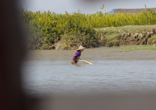 Woman fishing in a river with a net, Mrauk u, Myanmar