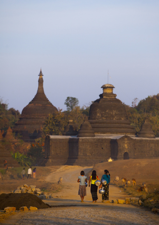Women carrying water in front of a buddhist temple, Mrauk u, Myanmar
