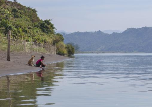 Woman washing clothes in kaladan river, Mrauk u, Myanmar