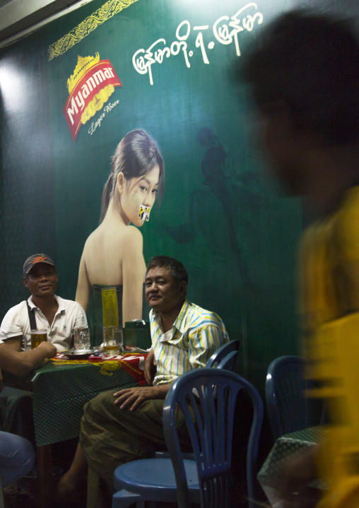 Men Inside A Bar In Front Of A Big Advertising, Yangon, Myanmar