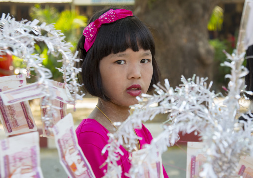 Girl walking to the temple with offerings for a novitiation ceremony, Bagan,  Myanmar