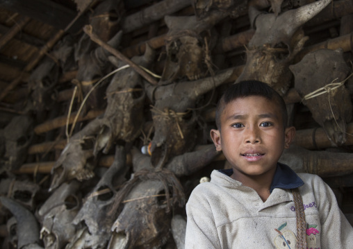 Chin boy in front of skulls at the entrance of his house, Mindat, Myanmar