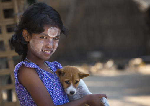 Girl with thanaka on cheeks carrying a dog, Ngapali, Myanmar