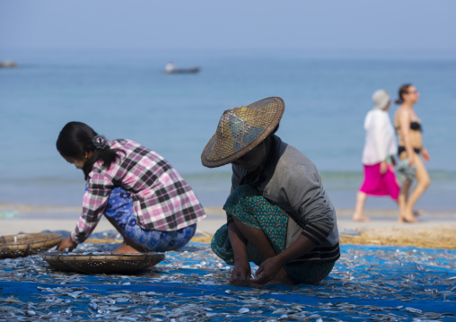 Women Putting Dried Fish On The Floor In Front Of Tourists Passing, Ngapali, Myanmar