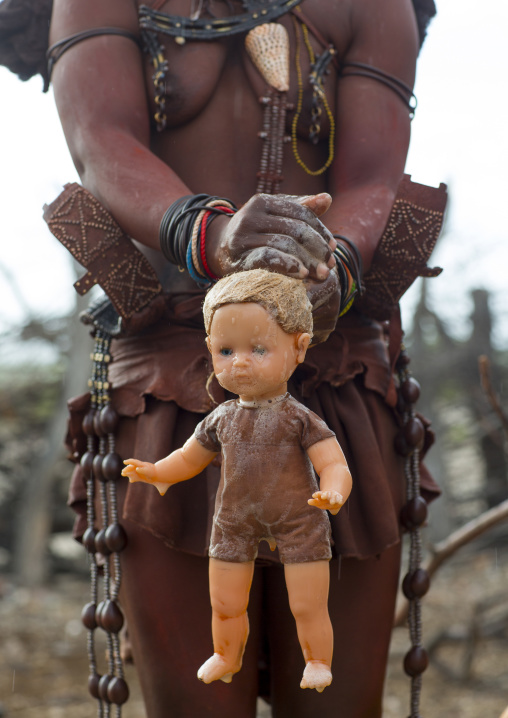 Himba Woman Washing A Blonde Doll, Epupa, Namibia