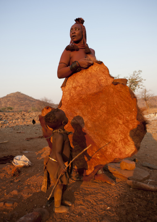 Himba Kid Looking At His Mother Holding A Skin, Okapale Area, Namibia