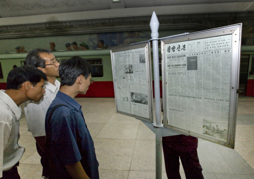 North Korean people reading the offical state newspaper in a subway station, Pyongan Province, Pyongyang, North Korea