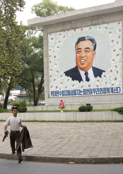 North Korean soldier running in front of a Kim il Sung fresco, North Hwanghae Province, Sariwon, North Korea
