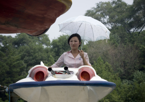North Korean woman having fun on a flying saucer attraction in Taesongsan funfair, Pyongan Province, Pyongyang, North Korea
