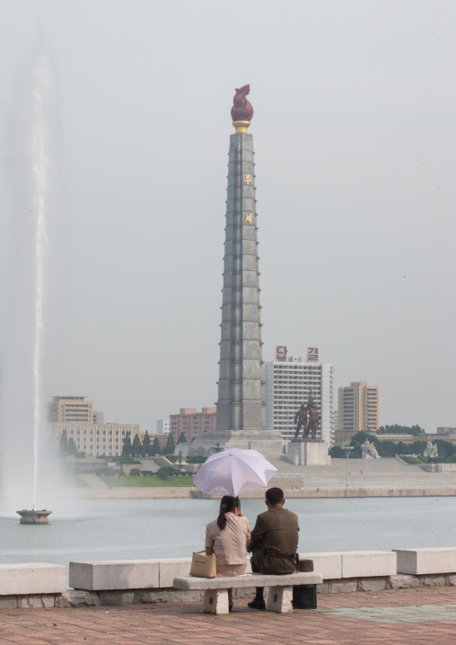 A North Korean soldier with his wife sitting on a bench in front of the Juche tower, Pyongan Province, Pyongyang, North Korea