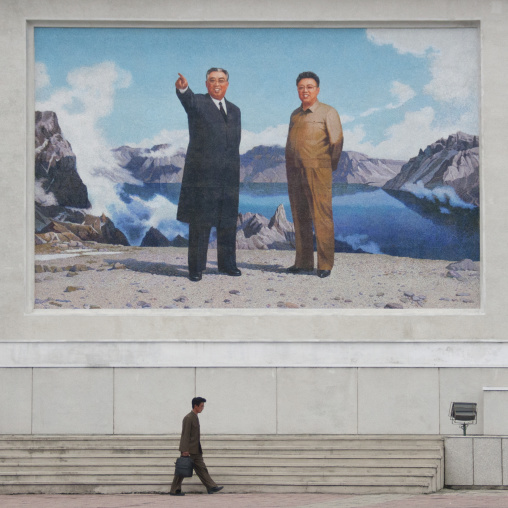 North Korean man passing in front of a giant fresco of Kim il and Sung Kim Jong il, Kangwon Province, Wonsan, North Korea