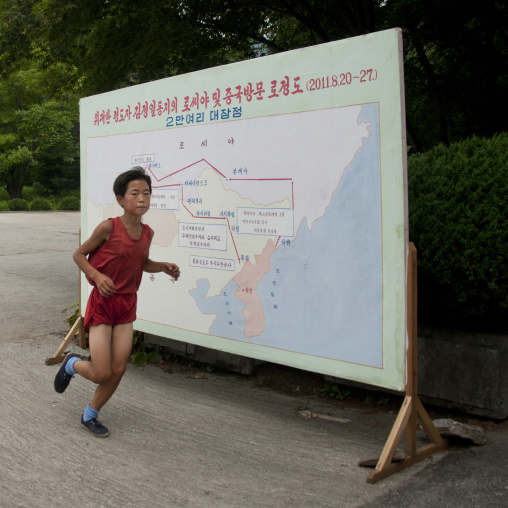 Young boy running in front of Kim Jong il last train trip map, South Hamgyong Province, Hamhung, North Korea