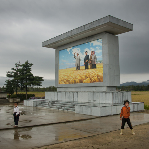 North Korean children in front of a fresco of the Dear Leaders with farmers, South Hamgyong Province, Hamhung, North Korea