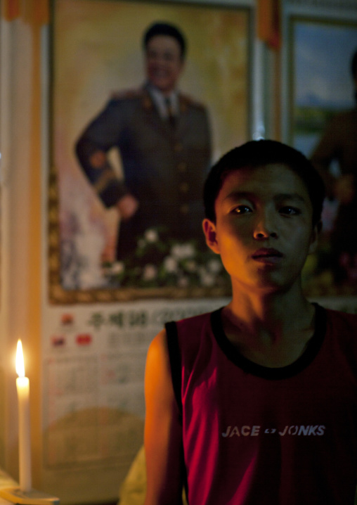 Portrait of a North Korean boy in a candlelit house in front of a Kim Jong-il portrait, North Hamgyong Province, Jung Pyong Ri, North Korea