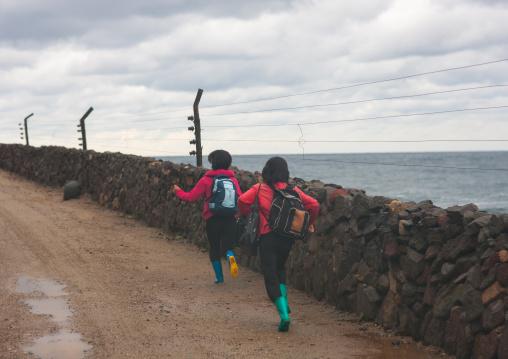 North Korean children running on a muddy road along a fence, North Hamgyong Province, Jung Pyong Ri, North Korea