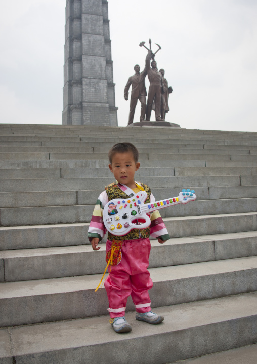 North Korean boy with a toy guitar on the stairs of the Juche tower built to commemorate Kim il-sung's 70th birthday, Pyongan Province, Pyongyang, North Korea