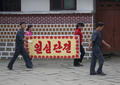 North Korean people carrying a propaganda bilboard i the street, North Hwanghae Province, Kaesong, North Korea