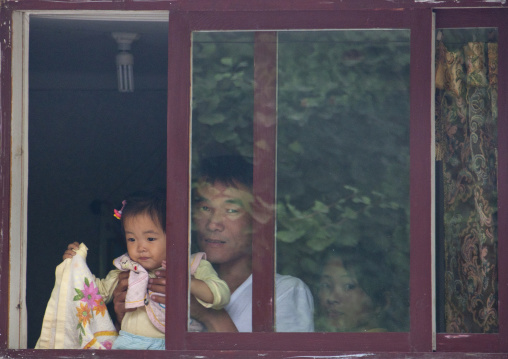 North Korean man holding her daughter through window frame, North Hwanghae Province, Kaesong, North Korea