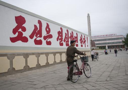 North Korean man passing in front of a propaganda billboard, North Hwanghae Province, Kaesong, North Korea