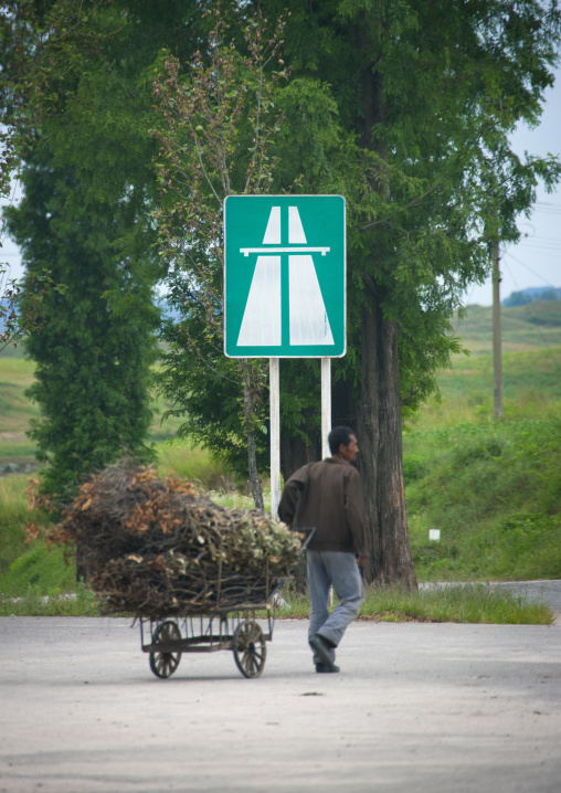 North Korean man with a cart full of wood in the Demilitarized Zone highway, North Hwanghae Province, Panmunjom, North Korea